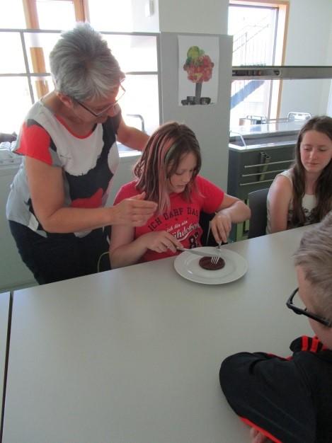 Frau Birk von der Knigge Gesellschaft zeigt Lana den richtigen Umgang mit Messer und Gabel.